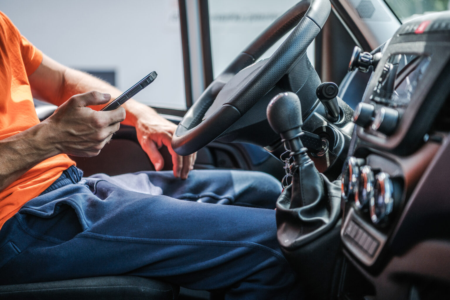 Delivery Truck Driver Browsing Internet Using His Smartphone